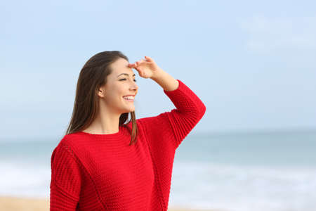 Happy girl in red scouting on the beach with the sea and horizon in the background Stock Photo