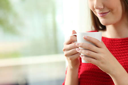 Close up of a relaxed woman hand holding a coffee cup at home