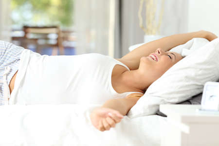Happy woman stretching arms waking up on the bed at home 스톡 콘텐츠