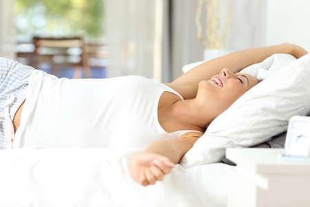Mujer feliz estirando los brazos despertando en la cama en casa