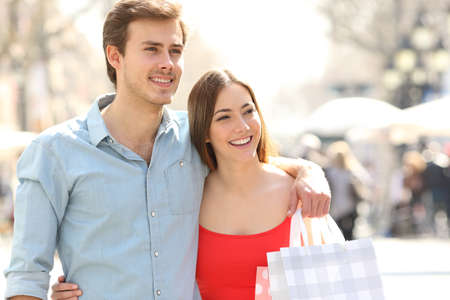 Front view portrait of a happy couple of shoppers walking in the street