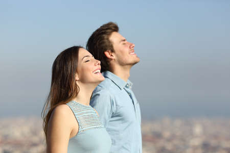 Side view portrait of a happy couple breathing fresh air with an urban background Foto de archivo