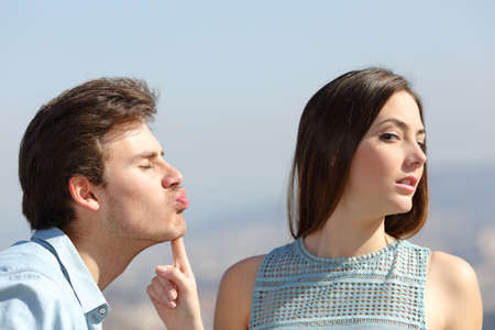 Woman rejecting a friend kiss in a sunny day Stock Photo