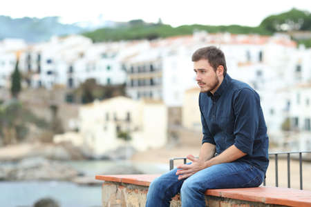 Worried man looking away sitting on a ledge in a coast town Stock Photo