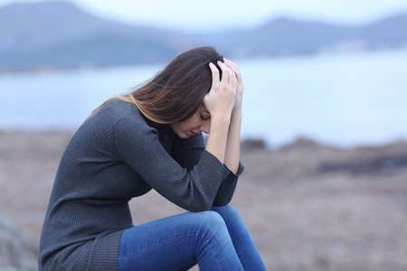 Sad woman complaining alone sitting on the beach a bad day
