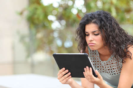 Bored woman watching media content in a tablet sitting in a park Stock Photo