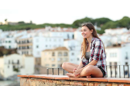 Happy teen contemplating views sitting on a ledge in a coast town on vacation Stock Photo