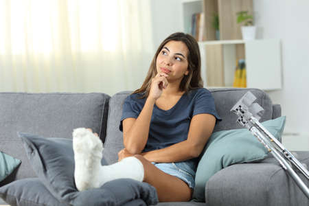 Disabled girl thinking looking at side sitting on a couch in the living room at home Stock Photo