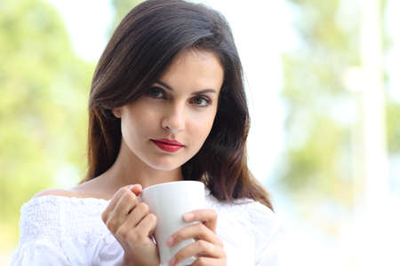 Front view portrait of a sexy woman holding a cup of coffee looking at camera outdoors Stockfoto