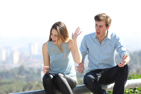 Angry couple arguing and shouting each other in a city outskirts Stock Photo