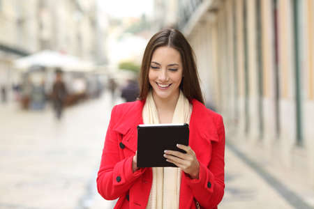 Front view portrait of a happy coman checking tablet content walking in the street Stock Photo