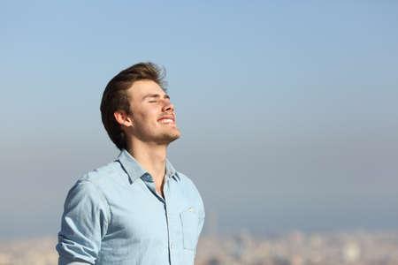 Hombre feliz respirando profundamente aire fresco en las afueras de la ciudad Foto de archivo