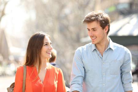 Vue de face d'un couple heureux marchant vers la caméra et parlant dans la rue