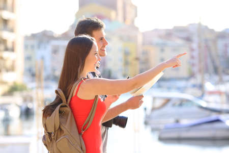 Happy couple of tourists pointing landmarks on vacation in a coast town