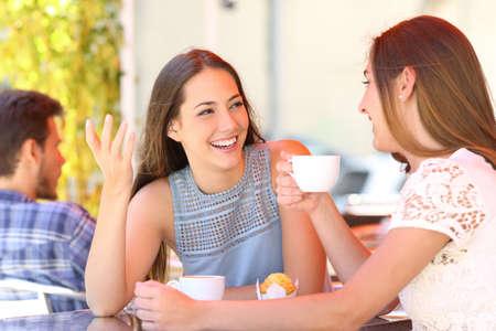 Due amici felici che parlano e bevono in una terrazza di una caffetteria Archivio Fotografico