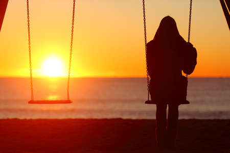Back view portrait of a single woman silhouette sitting on a swing contemplating sunset Foto de archivo