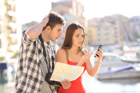 Lost couple of tourists trying to find locarion online in a smart phone in the street of a coast town Фото со стока