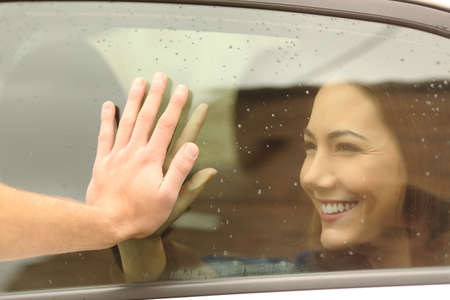 Happy couple or friends saying good bye touching hands through a car window before travel Stock Photo