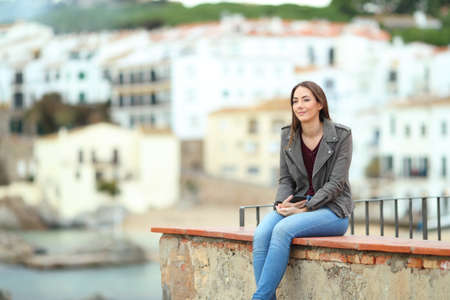 Relaxed woman contemplating ocean from a ledge in a coast town on vacation