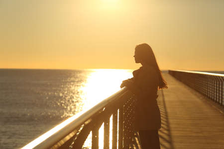 Woman alone contemplating ocean from a bridge at sunset on the beach