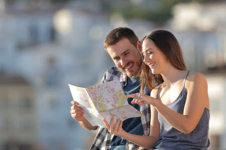 Couple of happy tourists checking paper guide in a town on vacation