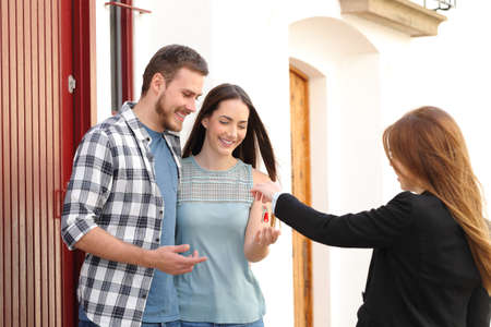 Happy couple of renters receiving house keys from real estate agent