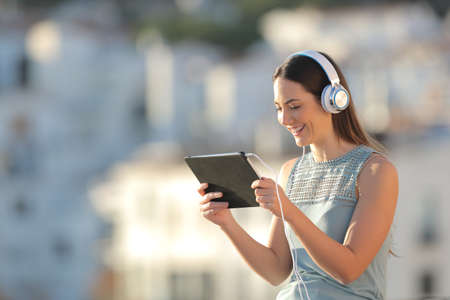 Happy woman watching media content in a tablet in a town Stock Photo