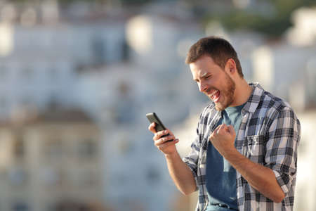 Excited man checking smart phone content in a town at sunset