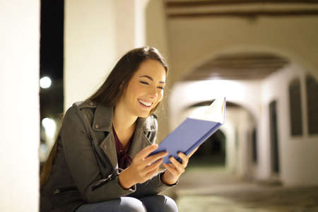 Happy woman reading a paper book sitting in the night in the street
