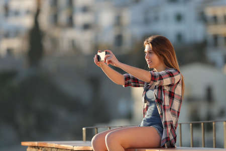 Happy teenage girl taking photos with a smart phone sitting on a ledge in a town outskirts