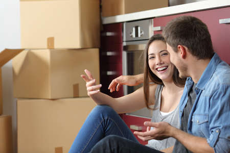 Smiley couple moving home talking on the floor of the kitchen Stock fotó