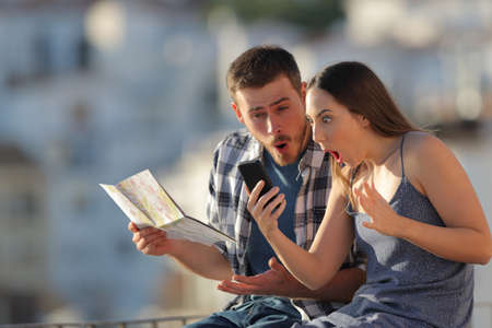 Amazed tourists finding online offers sitting on a ledge on vacation in a town