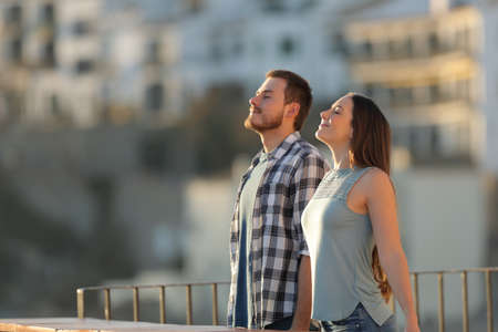 Happy couple in a town breathing fresh air from a rural apartment balcony Stock Photo