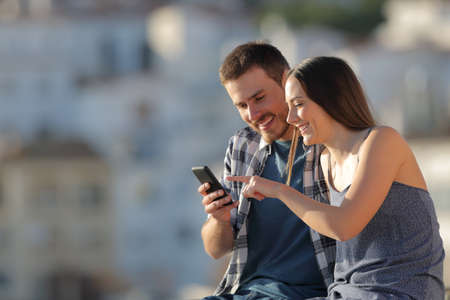 Happy couple browsing cell phone online content in a town outskirts Stock Photo