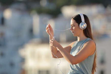 Frustrated woman fighting with the headphones cord in the street Stock Photo