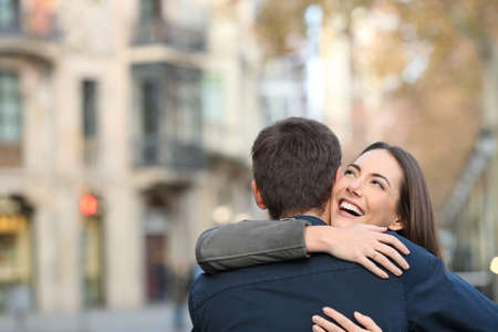 Couple cuddling after marriage proposal in the street with copy space