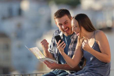 Aufgeregte Touristen, die das beste Angebot auf einem Smartphone finden, das auf einem Felsvorsprung in einer Stadt sitzt