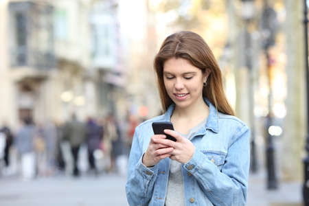 Portrait of a happy teen texting messages on a smart phone in the street