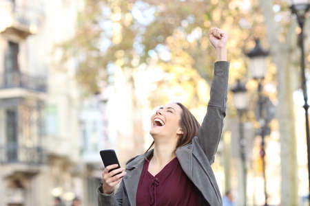Portrait of an excited woman holding smart phone and raising arm in the street