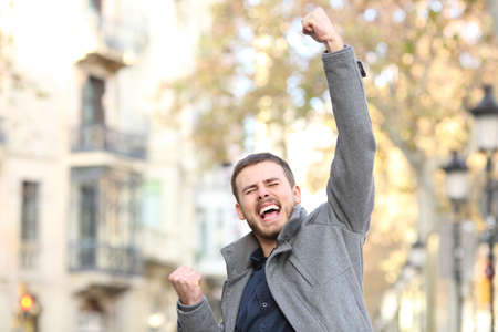 Portrait of an excited man raising arm in the street in winter