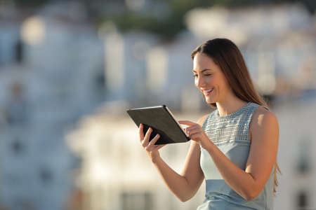 Happy woman browsing tablet online content in a town outskirts Stock Photo
