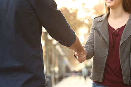 Close up of a happy woman and man hands handshking in the street Stock Photo