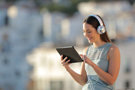 Happy woman litening to music browsing tablet content in a town at sunset Stock Photo