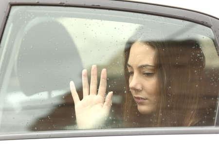 Sad woman touching window inside a car during a roadtrip a rainy day