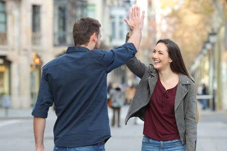 Zwei glückliche Freunde, die mitten auf der Straße High Five geben