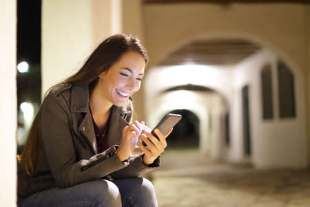 Happy female using a smart phone sitting in the night in the street