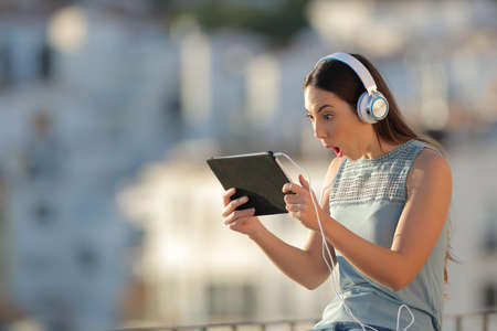 Amazed woman finds online content on a tablet sitting in a town at sunset Stock Photo