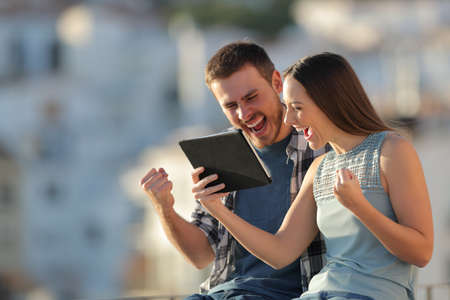 Excited couple checking tablet online content in a town on vacation at sunset Stock Photo
