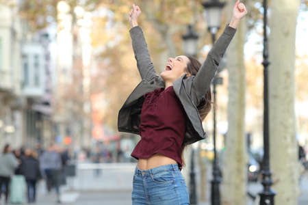 Excited woman jumping celebrating successs in the street
