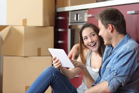 Happy couple moving home checking tablet online content sitting on the floor of the kitchen Stock Photo